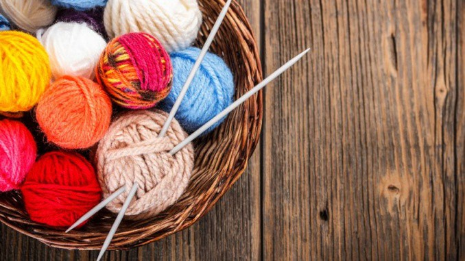 balls of yarn in a basket with knitting needles
