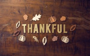 Thankful spelled out on a table with autumn leaves