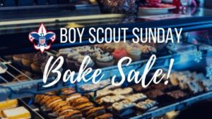 """pastries displayed in a bakery with """"Boy Scout Sunday - Bake Sale!"""" over"""