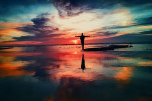 silhouette of person with outstretched arms on a beach during sunset