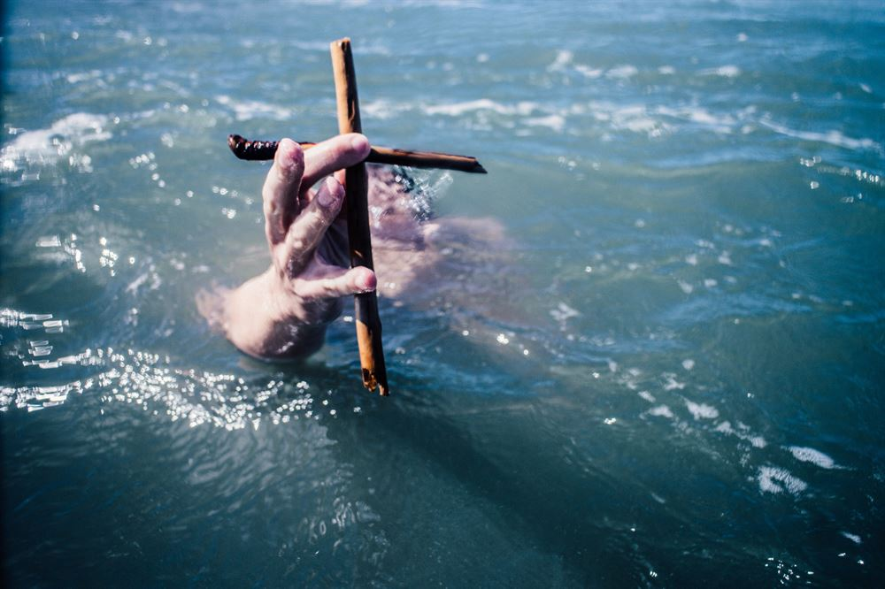 person under water holding cross above the water with hand
