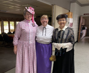 Three lovely women dressed in late 19th/early 20th century period costume, celebrating Heart of Longmont's 150th anniversary.